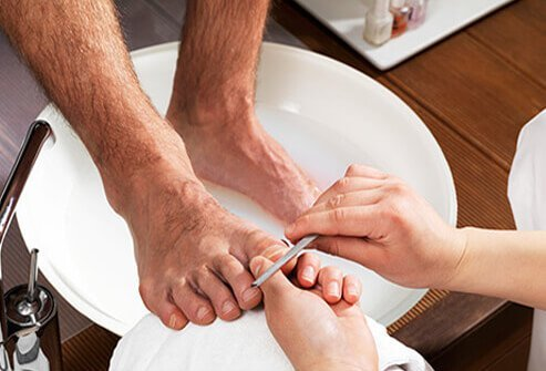 A man getting a foot bath and professional nail care.