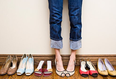 A woman stands among her collection of open toe shoes.