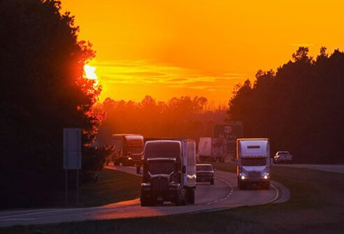 Photo of trucks on the highway at sunset.