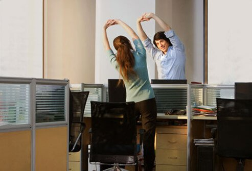 Photo of office workers doing stretches at night.
