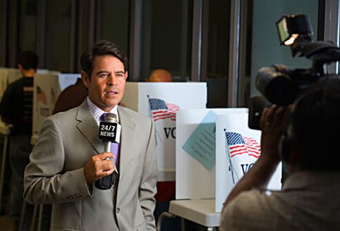 Photo of a cable news reporter at a polling station.