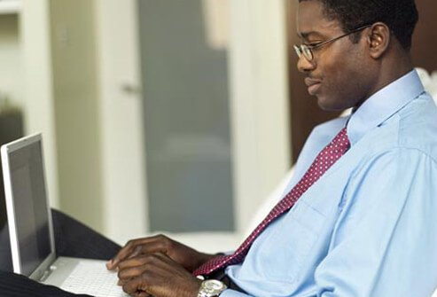 A man wearing eyeglasses and using a laptop.