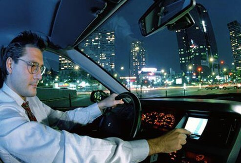 A man wearing eyeglasses and driving at night.