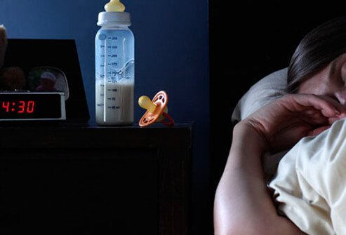A mother sleeping with a baby bottle and pacifier on the nightstand.