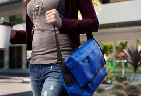 A woman carries a heavy tote bag.