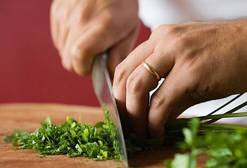 A woman chops herbs for cooking.