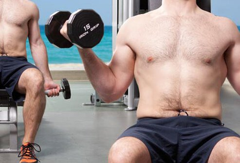 Photo of man using dumbbells.