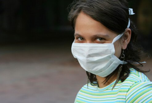 A young girl, contagious with mono, wears a mask.