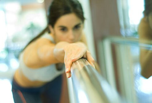 A woman uses a gym bar to stretch.