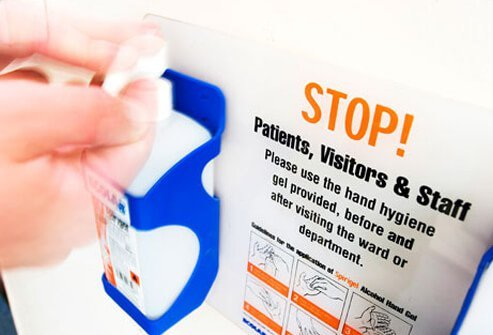 A hospital sign warns about hand hygiene.
