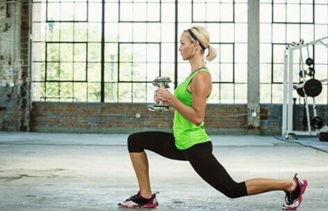 A woman doing lunges with weights.