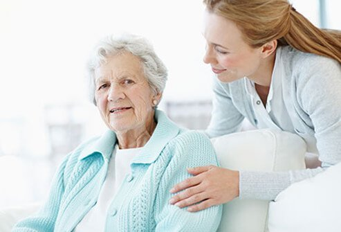 A caregiver comforting a senior woman with Alzheimer's disease.