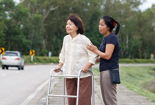 A senior woman with a walker being helped across the street by a caregiver.