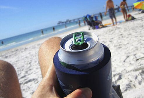 A person drinking out of an aluminum can at the beach.