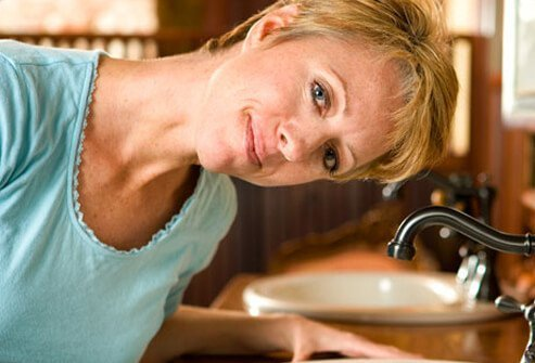 A woman tilting her head over the sink.