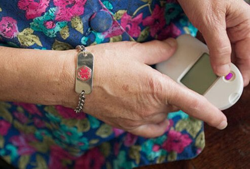 An elderly woman holding a blood glucose monitor.
