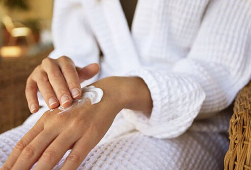 A woman applying topical cream to hand.