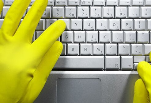 Gloved hands typing on computer keyboard.