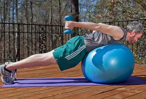 Photo of a man performing the ball plank with shoulder extension exercise.