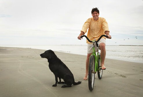 A man biking on a beach with his dog.