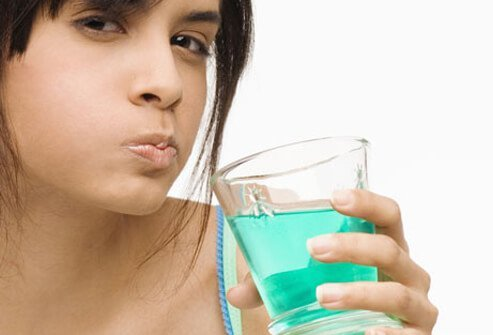 Young woman gargling with blue mouthwash.