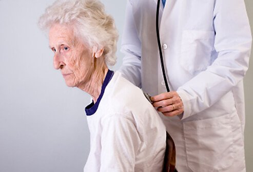 A senior woman with osteoporosis is examined by her doctor.
