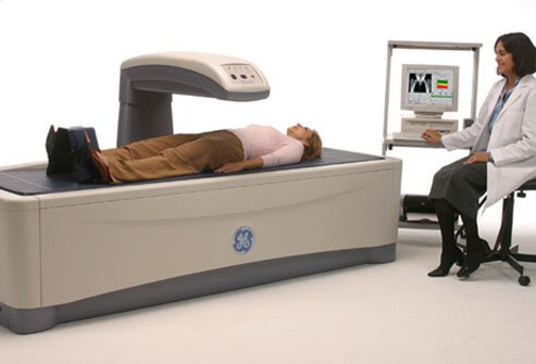 A doctor performs a DXA bone density scan on a female patient.