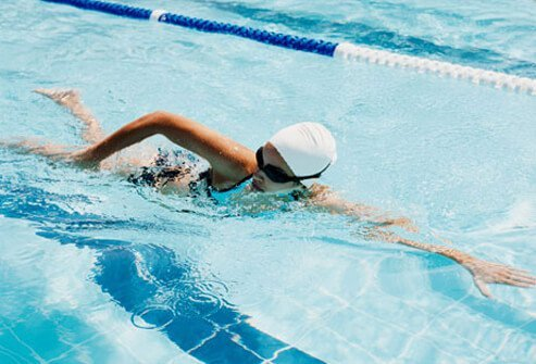 Photo of a woman swimming laps in a pool.