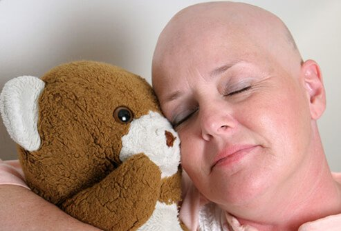 Woman that has lost her hair from chemo treatment hugs a teddy bear.