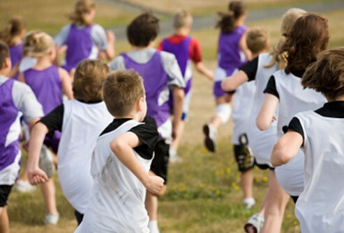 A group of kids runs during school P.E. class.