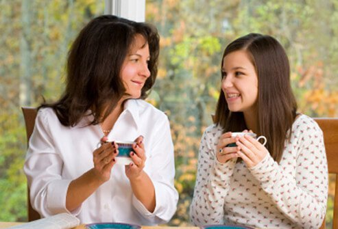 A mother and daughter have a discussion while drinking tea.