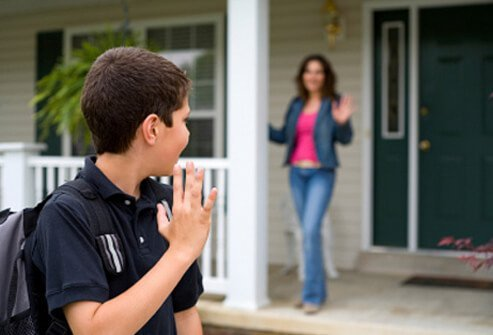 A son waves good-bye to his mother as he leaves for school.