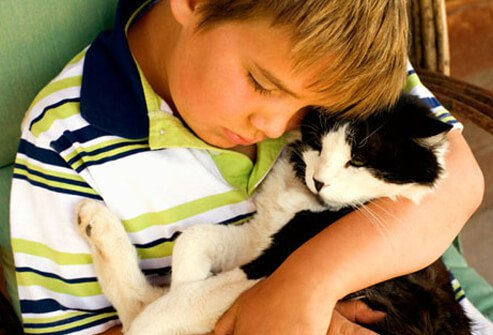 Photo of boy affectionately hugging cat.