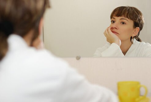 A woman stares in the mirror and wonders if her missed period could mean she is pregnant.