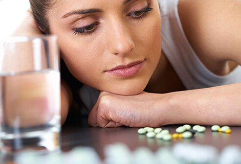 A woman stares at a dozen or so prescription pills laid out on a table.