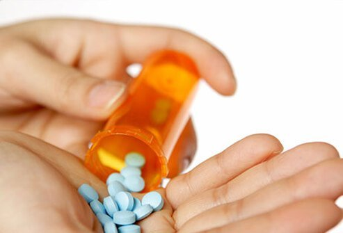 A woman pours prescriptions pills in to her hand.