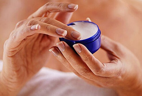 A woman putting thick cream onto her hands.