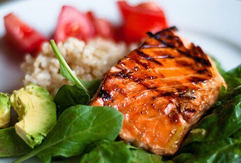 Cooked salmon on a full dinner plate.
