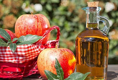 A photo of apples and vinegar on a table.