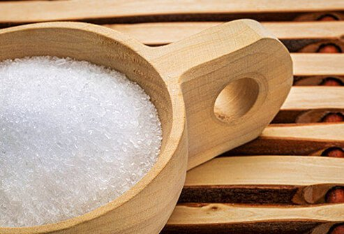 Salt grains in a wooden cup.