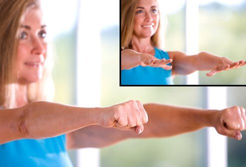 Woman demonstrating finger extensions and stretches to keep fingers flexible.