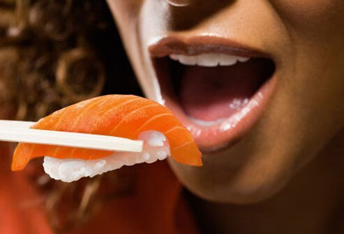 A woman eats a piece of salmon sushi.