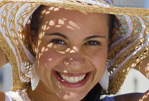 A woman wears a sun hat to protect her face.