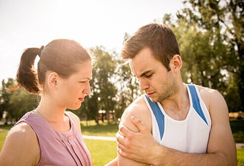 A woman looks at a man's injured shoulder.