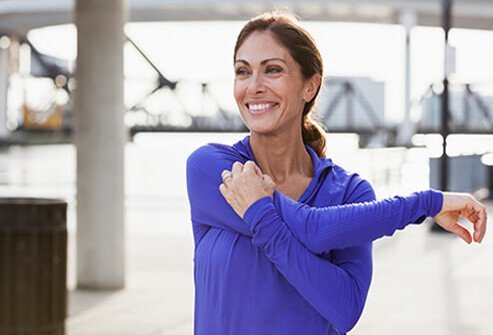 A woman stretching her shoulders before exercise.