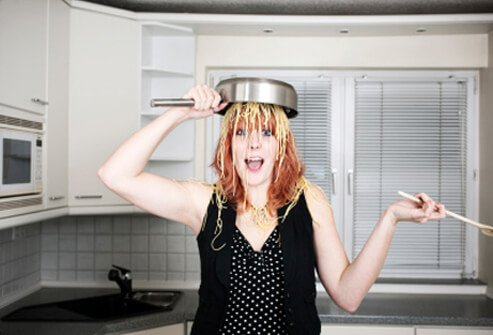 A young woman pours a pot of spaghetti on her head.