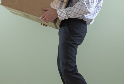 Photo of a man lifting a box.
