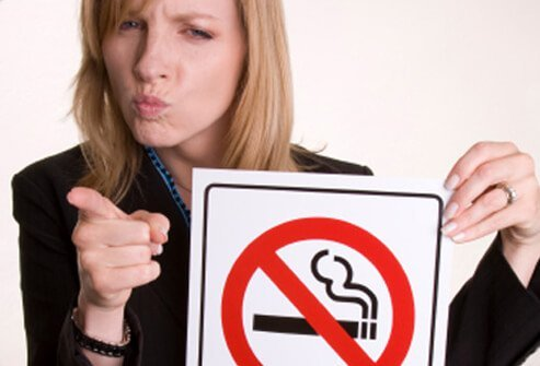 A woman points her finger and has a stern expression on her face while holding up a 'No Smoking' symbol.