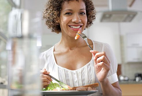 Photo of woman eating in kitchen.
