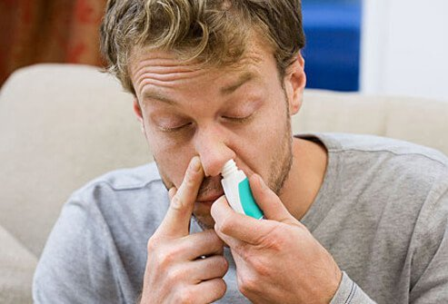 Man using nasal decongestant spray for sinus relief.